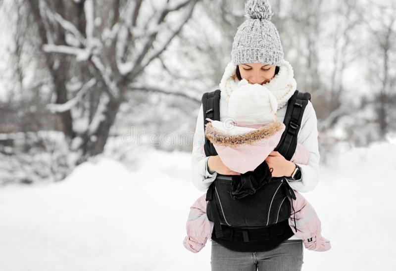 O bebê pequeno e sua mãe que andam fora na mãe do inverno estão guardando seu bebê que babywearing por conseguinte no portador fotografia de stock royalty free