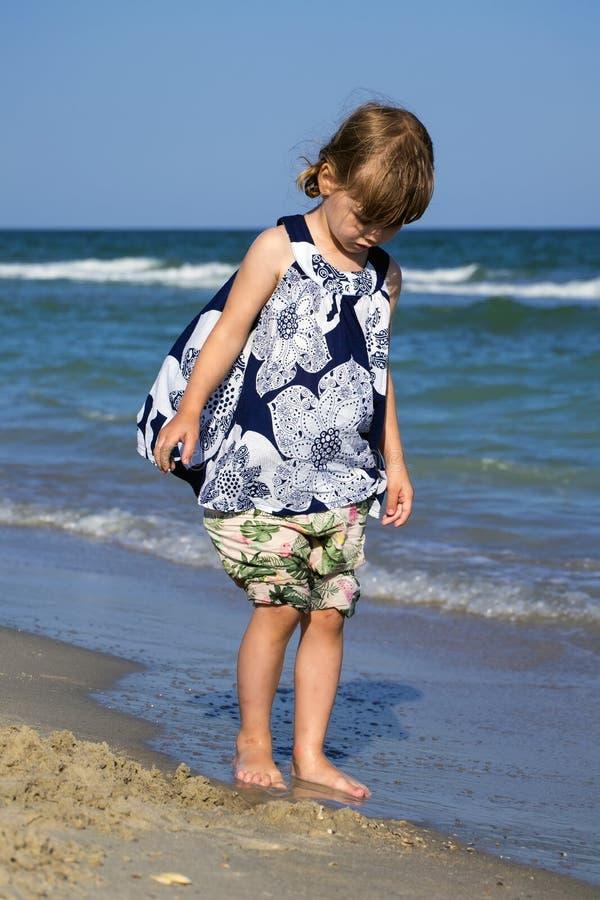 O bebê pequeno em um vestido florido está estando na costa de mar com sua cabeça para baixo e olhar como uma onda do mar lava seu fotos de stock