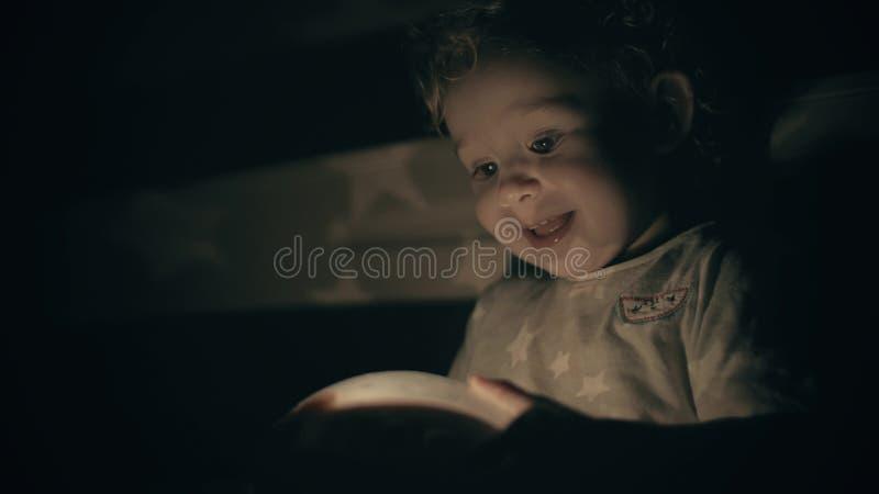 O bebê pequeno feliz olha o brinquedo de projeto luminoso na sala escura fotos de stock