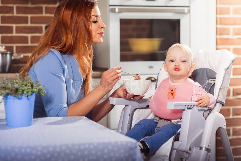 O bebê pequeno sent-se-ar na cadeira alta e em jogar um beijo quando mãe bonita que alimenta a com colher foto de stock