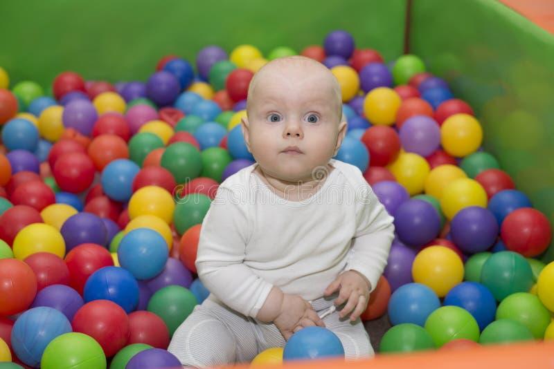 O bebê pequeno senta-se na associação com bolas imagens de stock