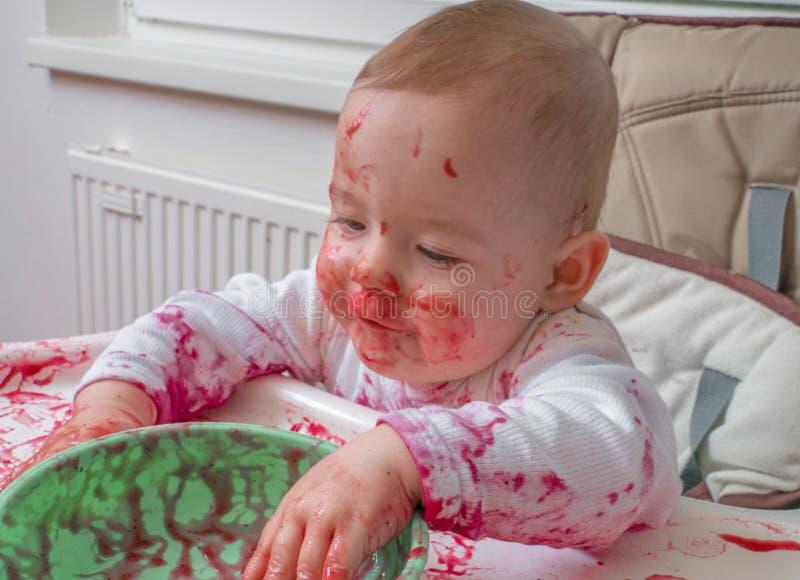 O bebê pequeno sujo desarrumado está comendo com mãos da bacia imagens de stock royalty free