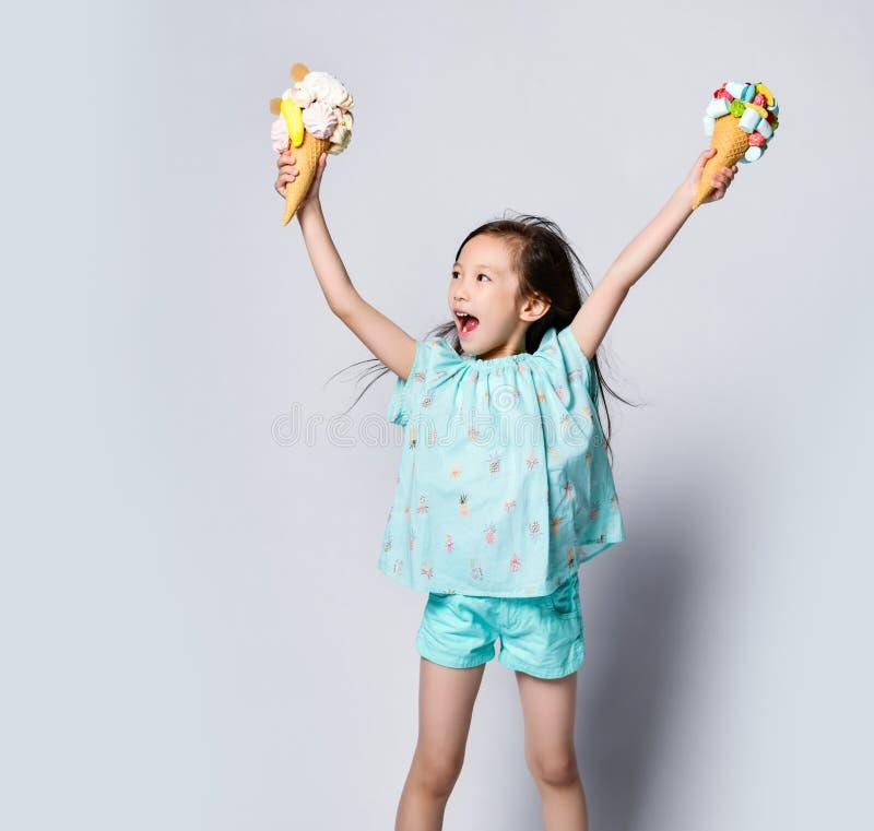 O bebê que feliz a criança a comemora tem o gelado dois grande em cones dos waffles com coberturas saborosos foto de stock