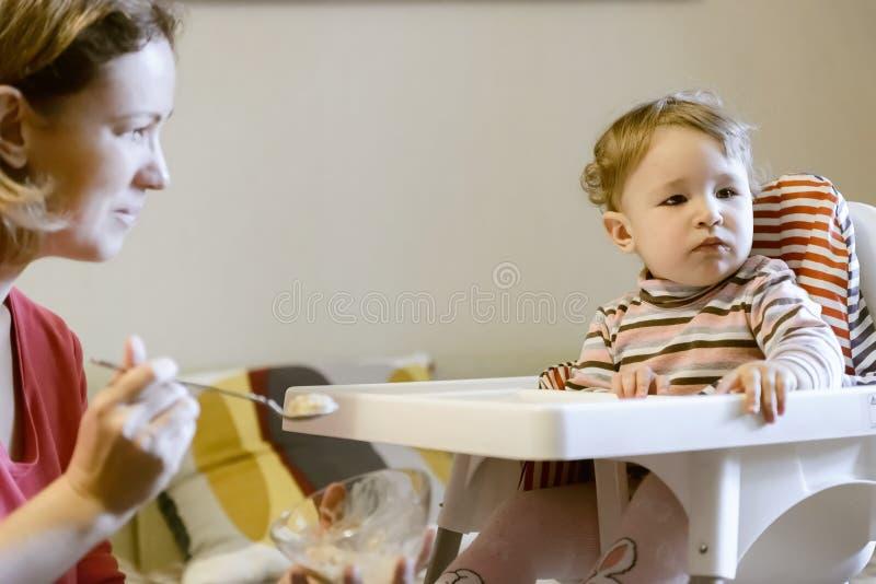 O bebê que senta-se no cadeirão e em sua mãe está alimentando do fotografia de stock royalty free