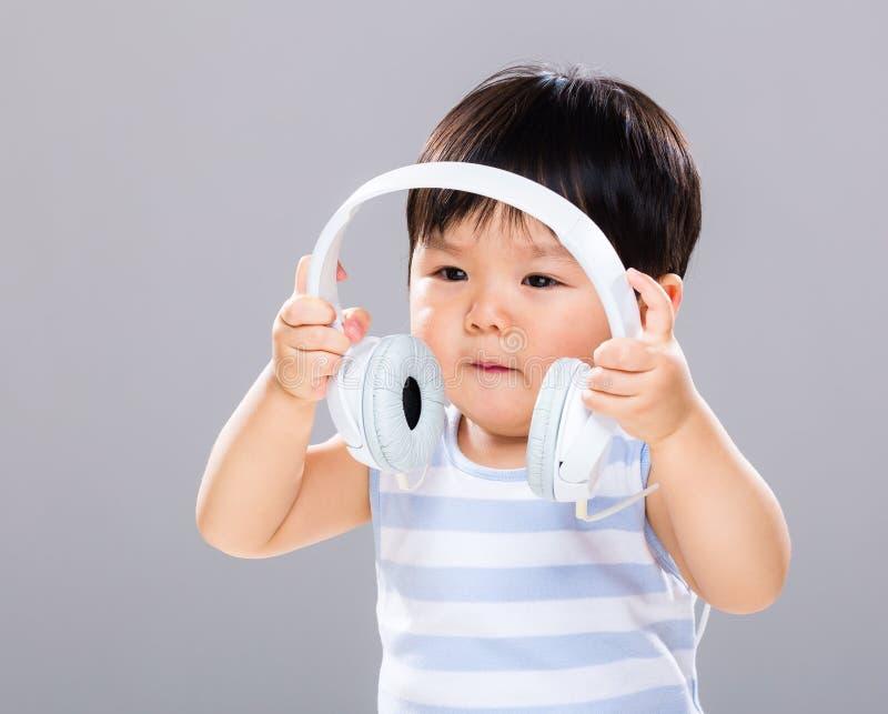O bebê quer escutar música usando o fones de ouvido fotos de stock