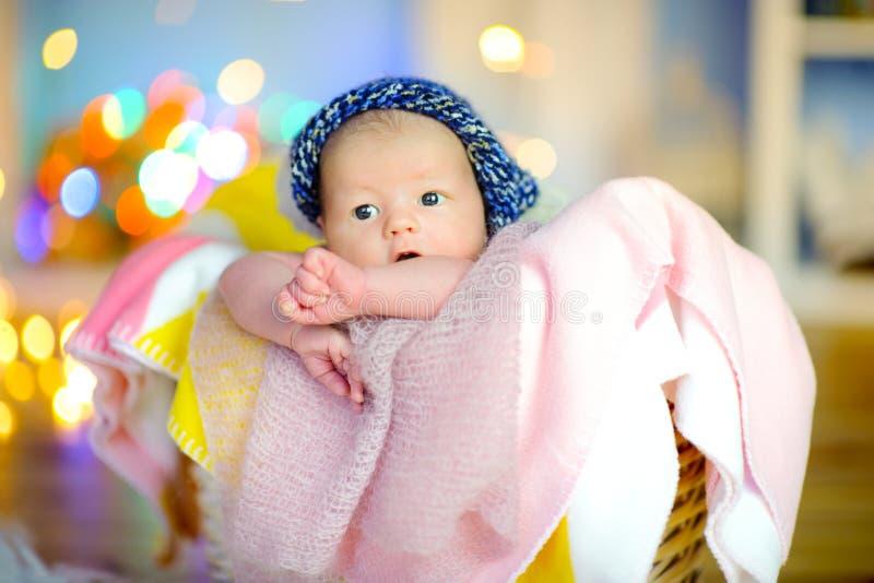 O bebê recém-nascido bonito em um chapéu engraçado encontra-se em uma cesta fotos de stock