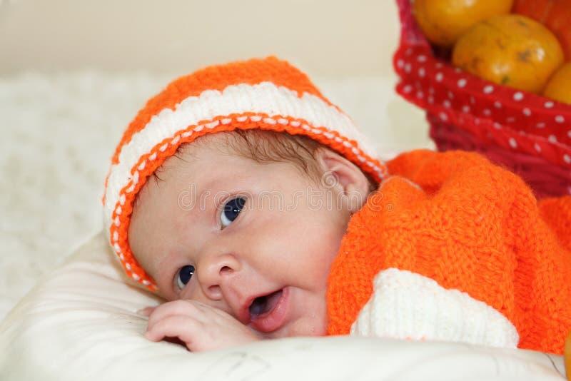 O bebê recém-nascido bonito surpreendido vestiu-se em um traje alaranjado feito malha fotos de stock royalty free