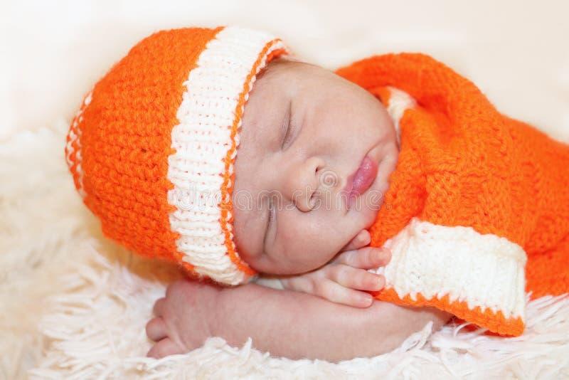 O bebê recém-nascido de sono calmo bonito vestiu-se em uma laranja feita malha fotografia de stock