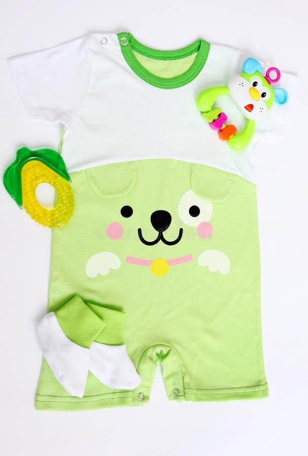 O bebê recém-nascido modelou o bodysuit com imagem de uma cara do cão, de montantes da malhas, de chocalho e de teether imagem de stock