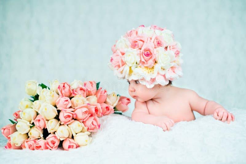 O bebê recém-nascido no chapéu aumentou sorrisos Retrato em um fundo branco imagens de stock