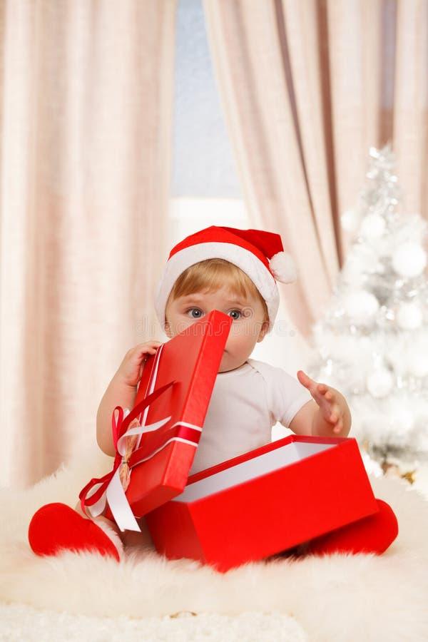 O bebê Santa guarda uma caixa de presente vermelha grande imagem de stock