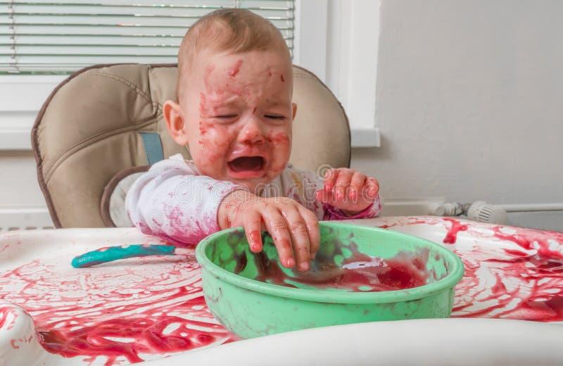 O bebê sujo desarrumado impertinente está comendo com mãos fotos de stock royalty free