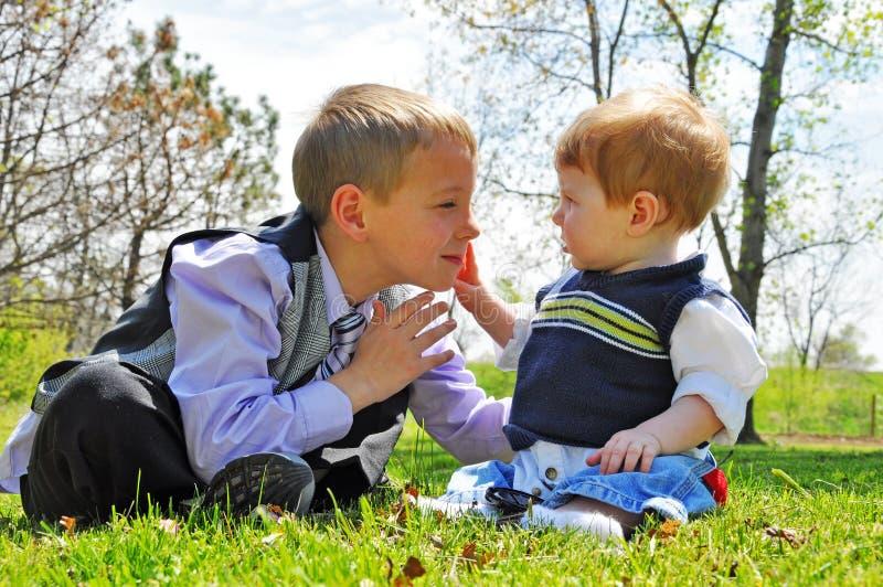 O bebê toca na cara dos meninos foto de stock