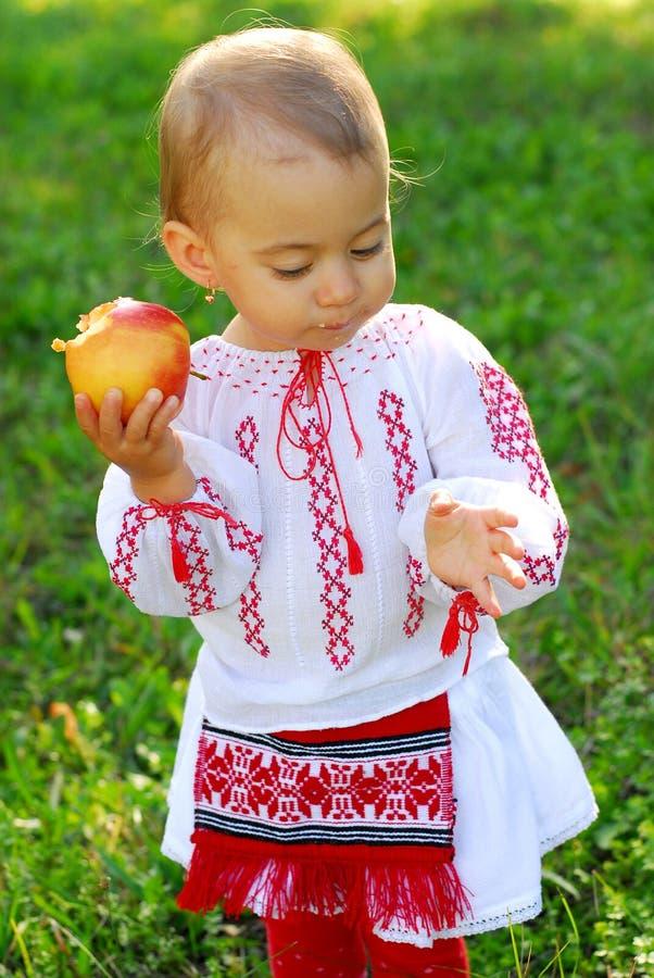O bebê vestiu-se no traje tradicional e em comer uma maçã foto de stock