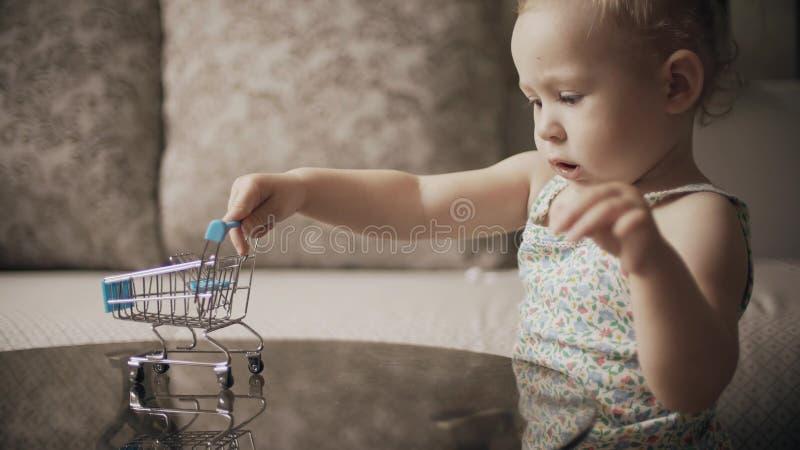 O beb? engra?ado joga com carrinho de compras do brinquedo imagens de stock royalty free