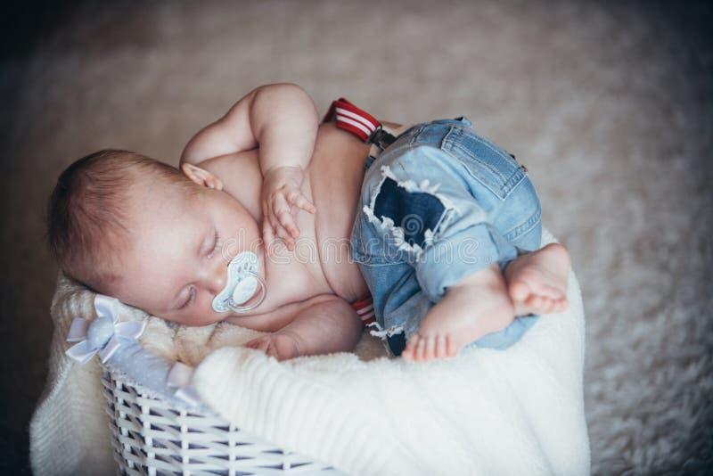 O beb? rec?m-nascido nas cal?as de brim dorme na cesta no assoalho fotos de stock royalty free