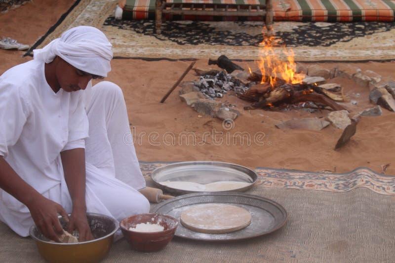 O beduíno prepara o pão em um acampamento do deserto em areias de Wahiba em Omã fotos de stock