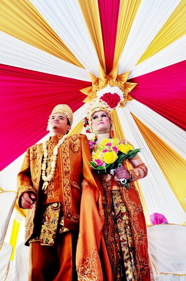 O beskap e o noivo muçulmanos do desgaste da noiva de Javanesse vestem o batik no casamento tradicional imagens de stock royalty free