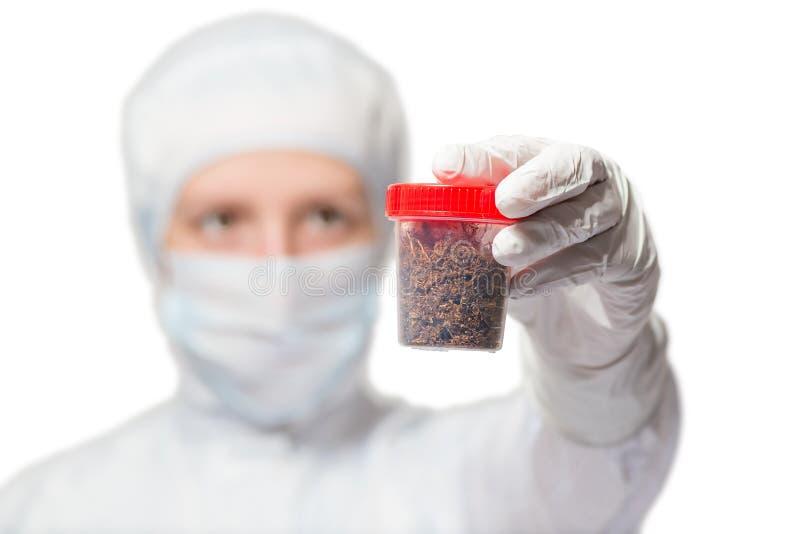 O biólogo mostra uma amostra do solo em um tubo de ensaio em um branco fotos de stock royalty free