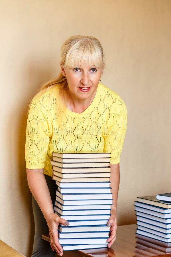 O bibliotecário de cinquenta anos de sorriso da mulher em um revestimento amarelo aumenta uma grande pilha de livros idênticos foto de stock royalty free