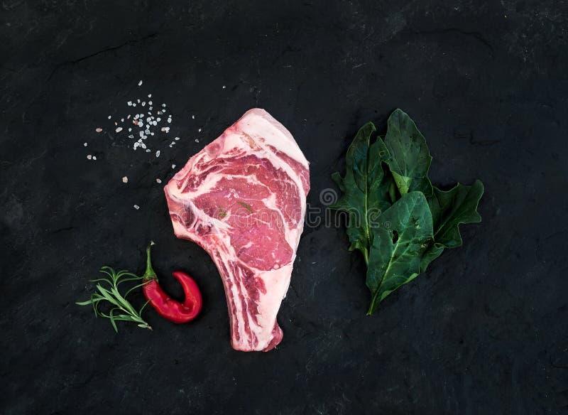 O bife cru do ribeye da carne fresca com sal, a pimenta de pimentão, os alecrins e os espinafres sobre a ardósia preta apedrejam  imagem de stock