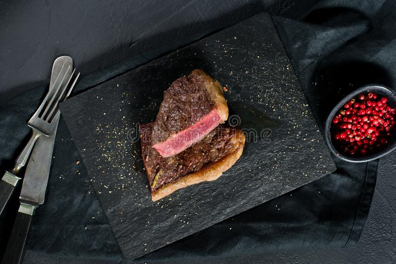 O bife de traseiro da carne roasted raro Fundo preto, vista superior foto de stock