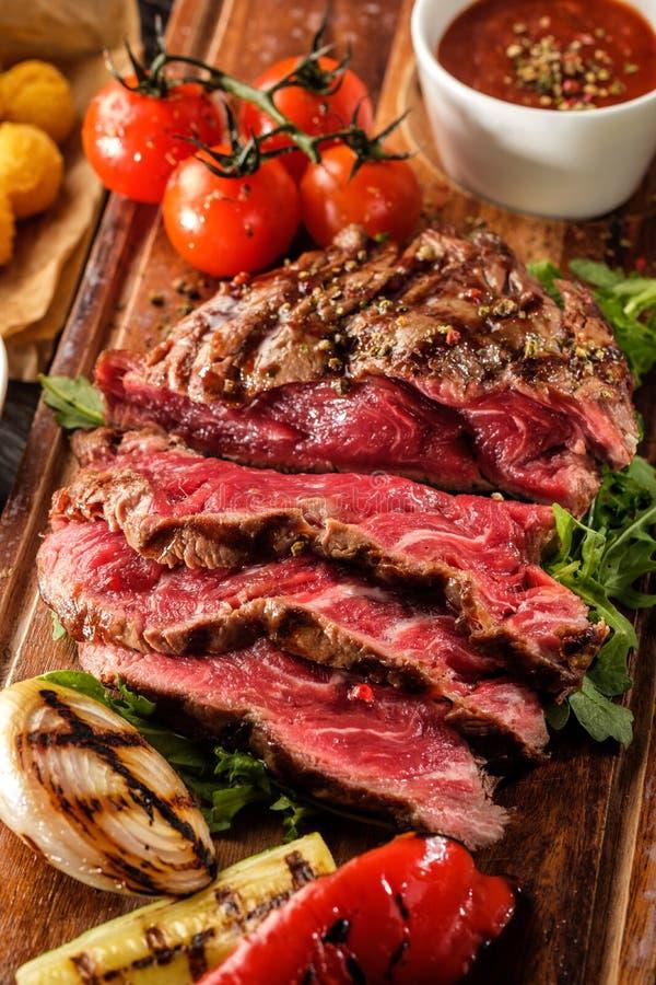 O bife de vaca grelhado cortado raro médio suculento serviu com tomate imagem de stock