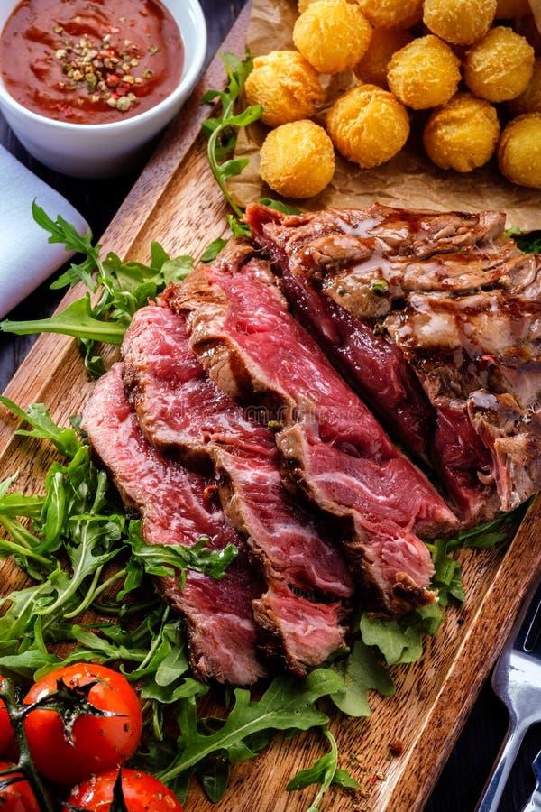 O bife de vaca grelhado cortado raro suculento serviu com tomates e fotografia de stock royalty free