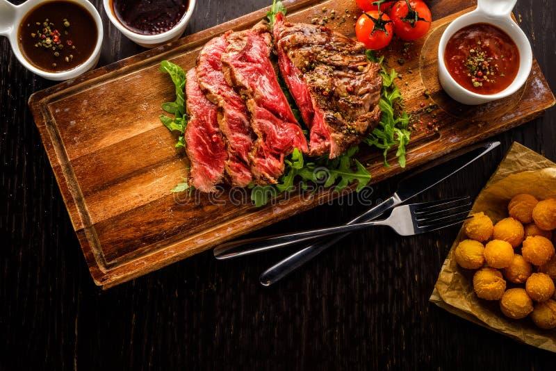 O bife de vaca grelhado cortado raro suculento serviu com tomates e imagem de stock royalty free