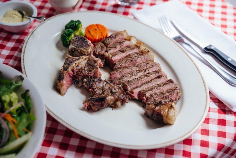 O bife do lombo grelhado carvão vegetal cortado do wagyu serviu com molho do BBQ na placa branca na toalha de mesa vermelha e bra fotos de stock royalty free