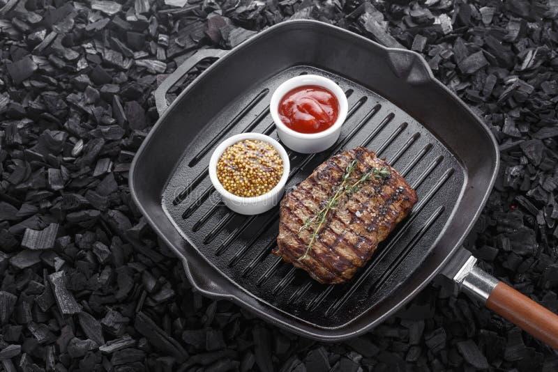 O bife grelhado cozinhou em uma frigideira imagem de stock