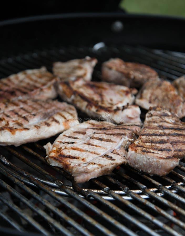 O bife grelhado da carne, partes de carne postas de conserva é grelhado na grade barbecue fotografia de stock royalty free