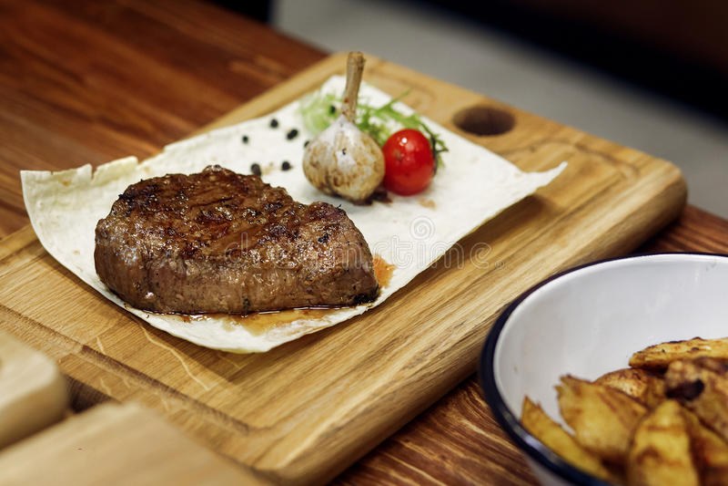 O bife grelhado suculento com potatos fritados salpica o tomate e o alho foto de stock royalty free