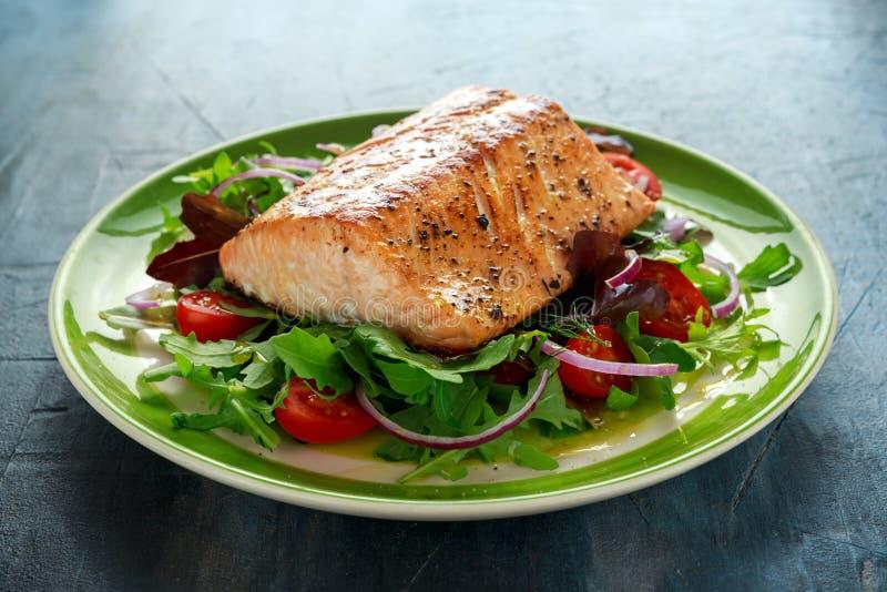 O bife salmon cozido com tomate, cebola, mistura de verde deixa a salada em uma placa Alimento saudável imagens de stock