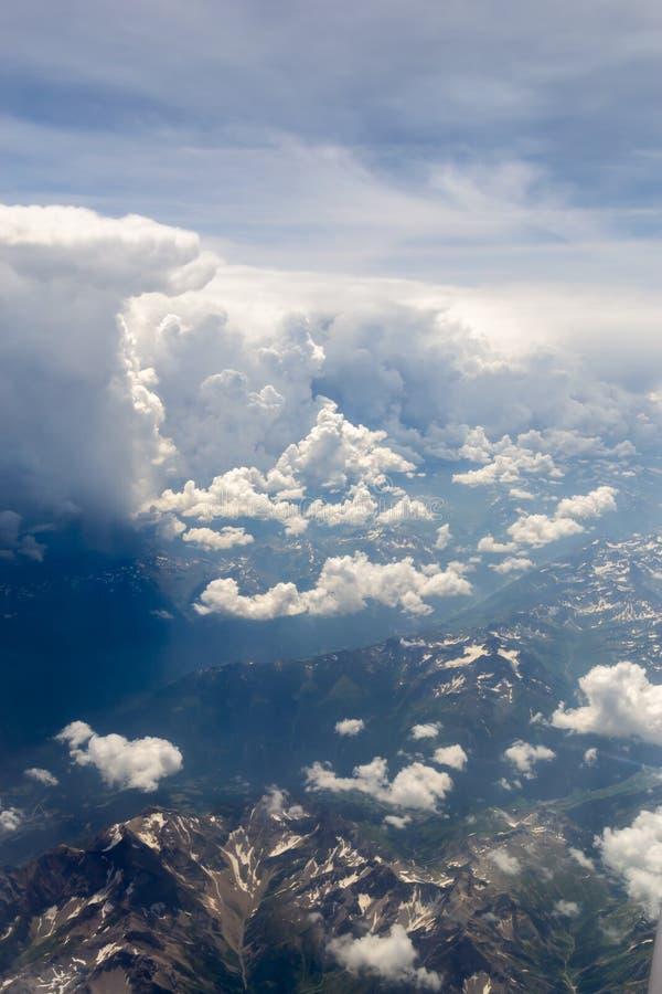 O bird' opinião do olho de s no céu com as nuvens dramáticas macias enormes acima dos cumes foto de stock