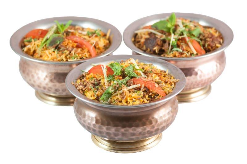 O biryani indiano do risoto no metal ou no bronze rola no fundo branco foto de stock royalty free