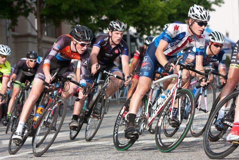 O bloco apertado dos ciclistas inclina-se na volta na raça amadora foto de stock