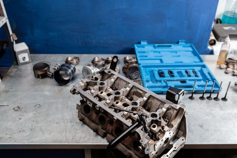 O bloco de motor desmontado está na tabela O mecânico abriu o mecanismo de travamento da válvula Reparo do capital do motor imagem de stock royalty free