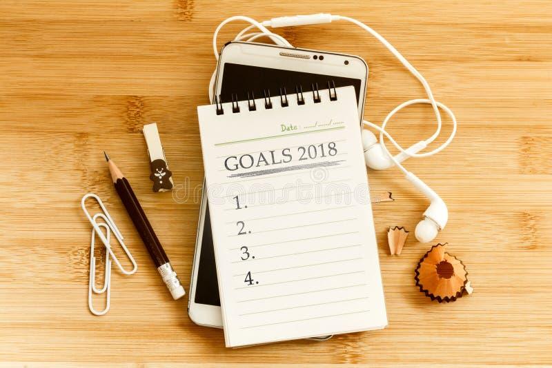 O bloco de notas com lápis e o telefone esperto para ajustar os OBJETIVOS 2018 imagem de stock