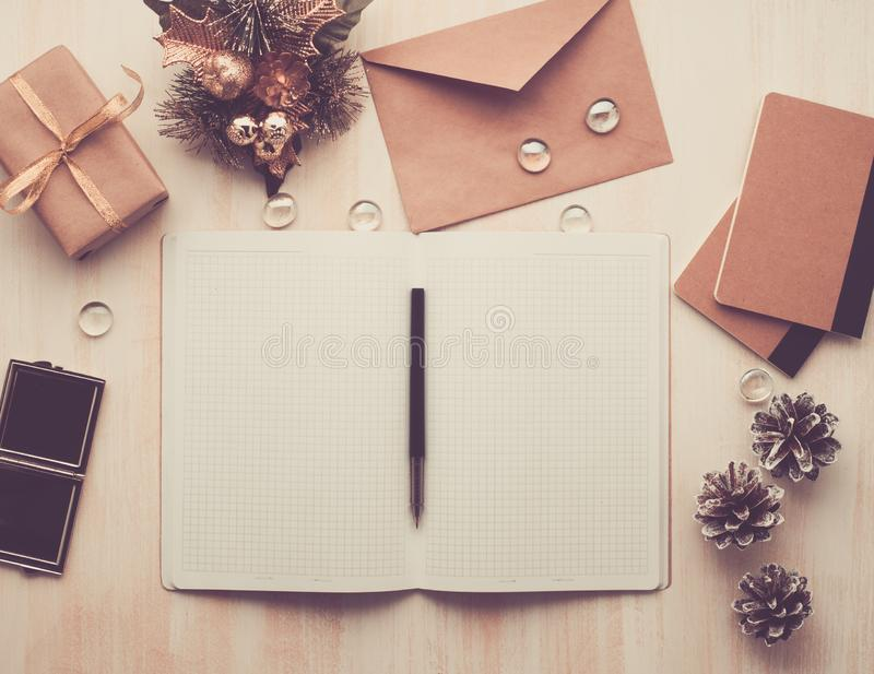 O bloco de notas do branco, o envelope aberto e a decoração do Natal que encontra-se no fundo de madeira bege, horizontalmente co foto de stock