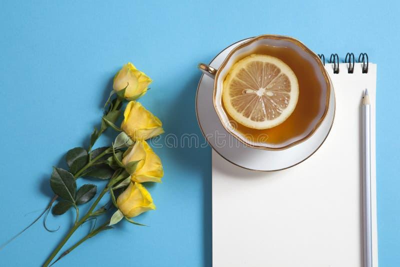 O bloco de notas quadrado nas molas com papel de embalagem branco, o lápis, a rosa do amarelo e o copo do chá estão em um fundo a fotos de stock royalty free