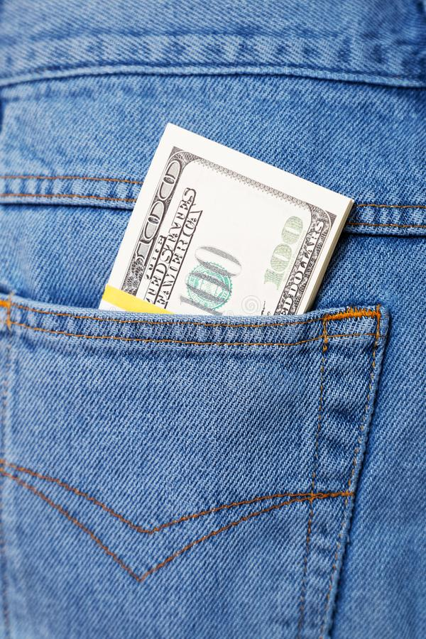 O bloco dos dólares que colam fora do calças de brim pocket fotos de stock
