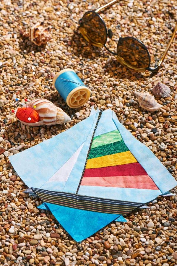 O bloco dos retalhos, o carretel da linha, o coxim do pino e os óculos de sol encontram-se em pedras do mar da praia imagem de stock royalty free