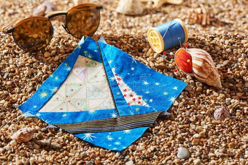 O bloco dos retalhos, o carretel da linha, o coxim do pino e os óculos de sol encontram-se em pedras do mar da praia foto de stock royalty free
