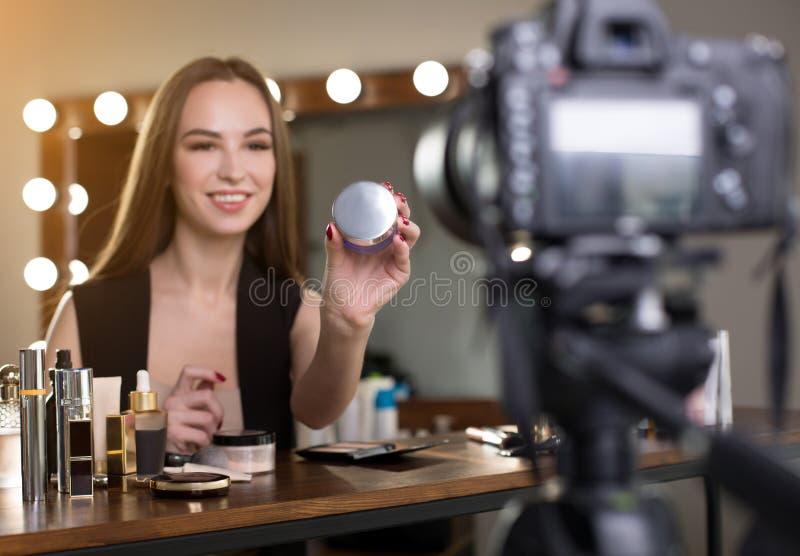 O blogger alegre da beleza está demonstrando o produto novo imagem de stock royalty free