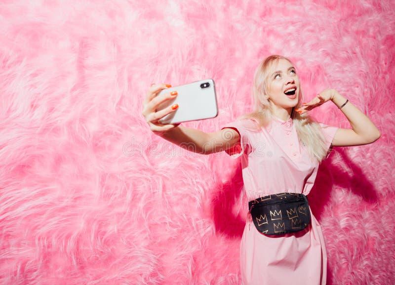 O blogger brilhante da mo?a vestido no vestido cor-de-rosa da forma toma um selfie em seu smartphone no fundo da pele cor-de-rosa fotografia de stock royalty free