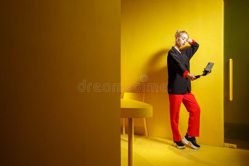 O blogger da moça da forma vestido na calças vermelha e no revestimento preto toma um selfie em seu smartphone na sala com foto de stock