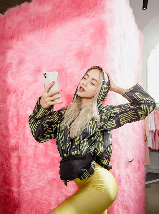 O blogger da mo?a da forma vestido em um revestimento preto e amarelo ? moda e em um short amarelo toma um selfie no imagens de stock royalty free
