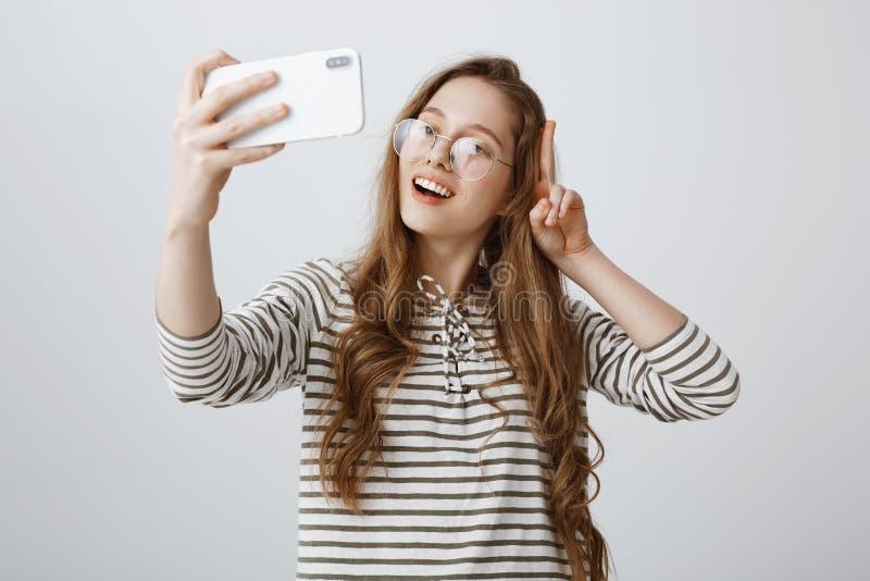 O blogger popular da forma faz o vlog novo usando o smartphone Retrato da menina europeia segura positiva que mostra o sinal de v imagens de stock
