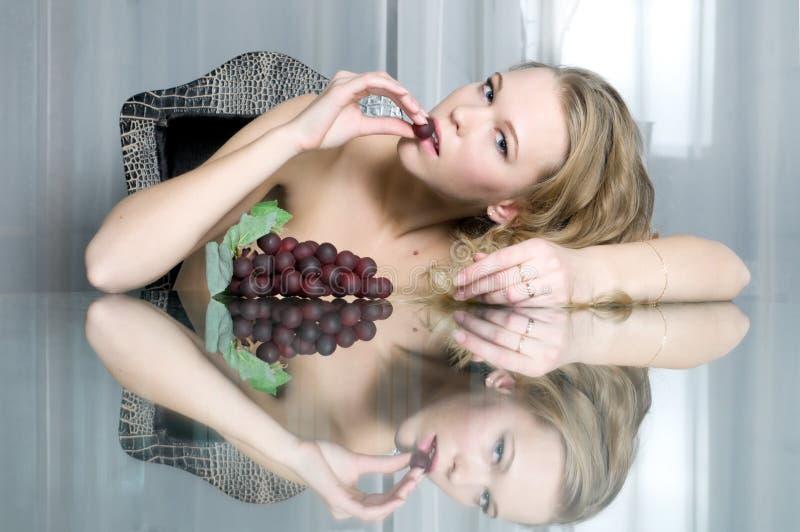 O blonde bonito está comendo a uva fotografia de stock royalty free